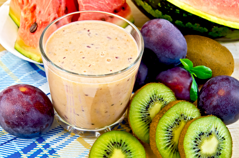 Milk shake in a glass beaker with plums, kiwi and watermelon on a napkin on the background of wooden boards